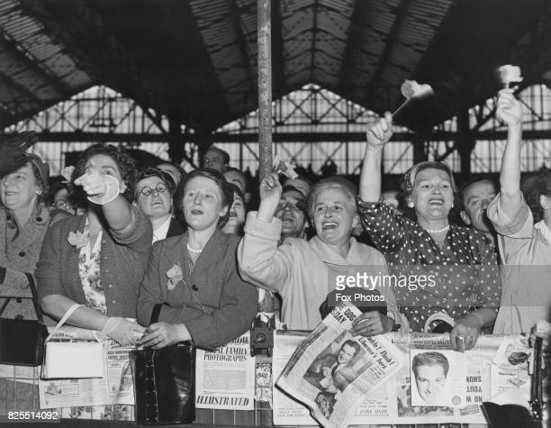 Fans of American pianist and singer Liberace born Wladziu Valentino Liberace gather at Waterloo Station in London to meet their idol off the 'Queen...