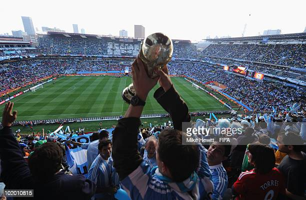 Fans of Argentina enjoy the atmosphere with a replica of the World Cup trophy during the 2010 FIFA World Cup South Africa Group B match between...