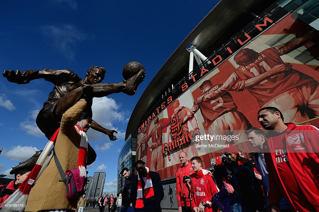Fans of Arsenal enjoy the new former Arsenal and Netherlands footballer Dennis Bergkamp statue prior to the Barclays Premier League match between Arsenal and Sunderland at Emirates Stadium on February 22, 2014 in London, England.