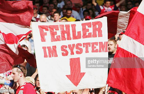Fans of Bayern Munich hold up a banner saying 'error in the system' during the Bundesliga match between VfB Stuttgart and Bayern Munich at the...