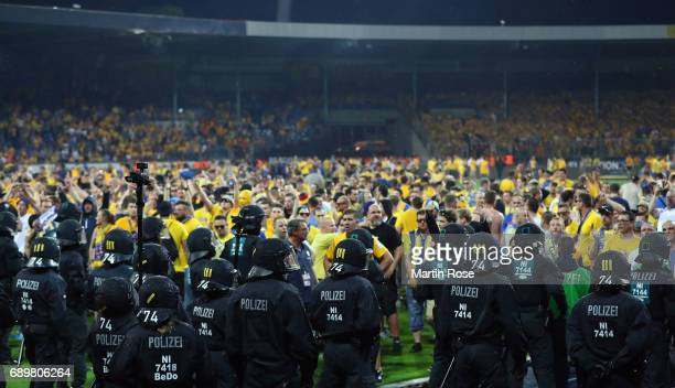 Fans of Braunschweig face police in riot gear after the Bundesliga Playoff leg 2 match between Eintracht Braunschweig and VfL Wolfsburg at Eintracht...
