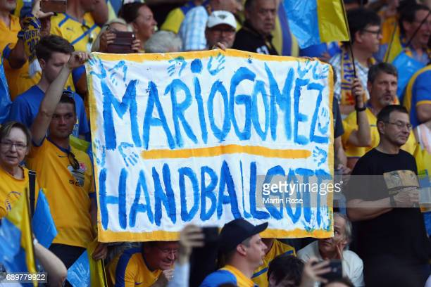 Fans of Braunschweig hold up a placard to tease Mario Gomez of Wolfsburg prior to the Bundesliga Playoff leg 2 match between Eintracht Braunschweig...