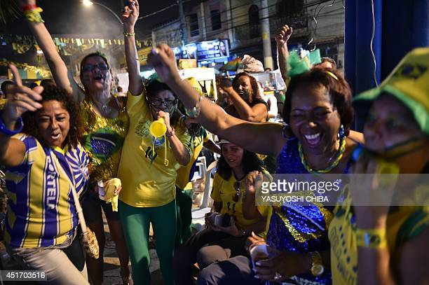Fans of Brazil celebrate as they watch live television footage outside the Portela Samba School in Rio de Janeiro on July 4 after Brazil's defender...