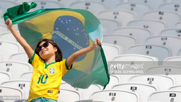 TOPSHOT Fans of Brazil cheer their team during the Rio 2016 Olympic Games women's bronze medal football match Brazil vs Canada at the Arena...
