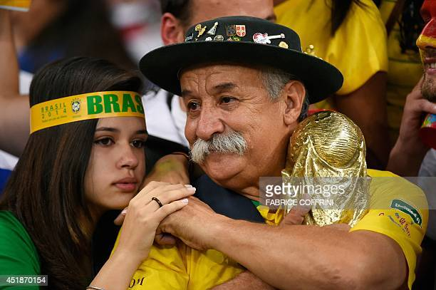 Fans of Brazil reacts after their team lost the semifinal football match between Brazil and Germany at The Mineirao Stadium in Belo Horizonte during...