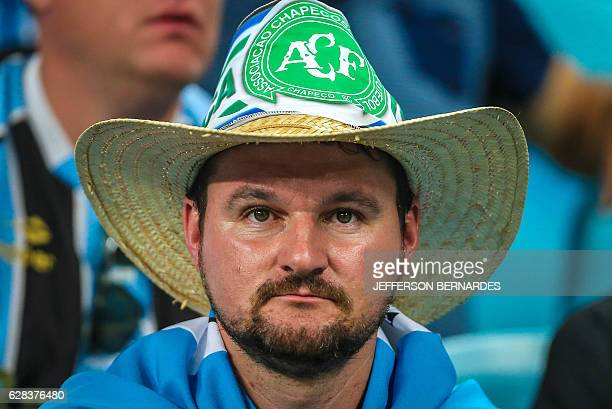 Fans of Brazil's Gremio wear the bdget of the Chapecoense football club before the start of the 2016 Brazil's Cup final football match against...
