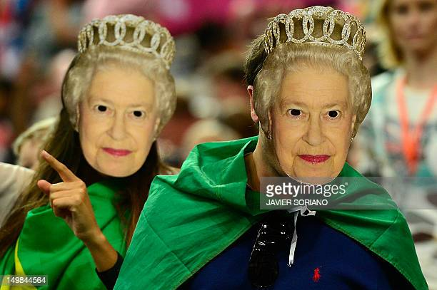 Fans of Brazil's handball team wearing a mask depicting Queen Elizabeth II pose after the women's preliminary Group A handball match Brazil vs Angola...
