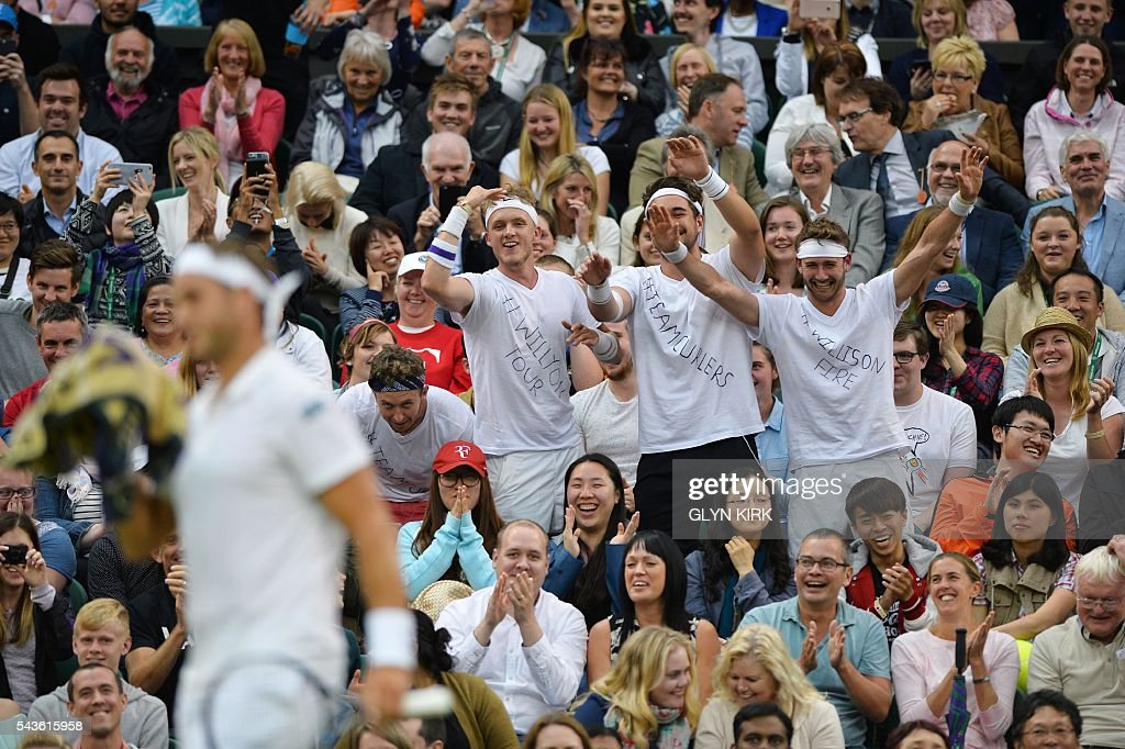 Fans of Britain's Marcus Willis celebrate in the crowd as Willis plays against Switzerland's Roger Federer in their men's singles second round match on the third day of the 2016 Wimbledon Championships at The All England Lawn Tennis Club in Wimbledon, southwest London, on June 29, 2016. / AFP / GLYN