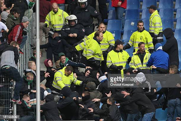 Fans of Brmeen and fans of Hamburg fight against each othe prior to the Bundesliga match between Hamburger SV and Werder Bremen at Imtech Arena on...