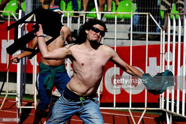 Fans of Chile's Colo Colo and Wanderers football teams fight on the field prior to the first division football match at the Elias Figueroa stadium in...