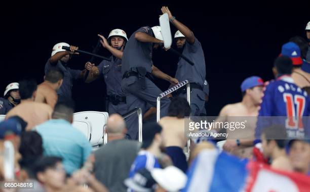 Fans of Chile's Universidad throw chunks of seats to the riot police during the Copa Sudamericana match between Corinthians and Universidad Chile at...