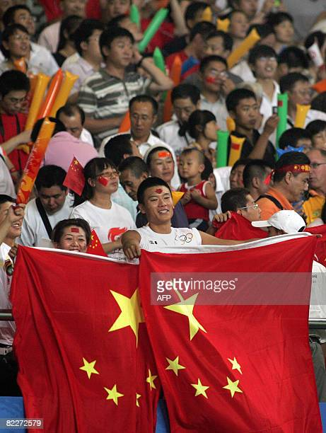 Fans of China cheer and wave the country's flag for their team during the 2008 Beijing Olympic Games first round Group E women's football match...