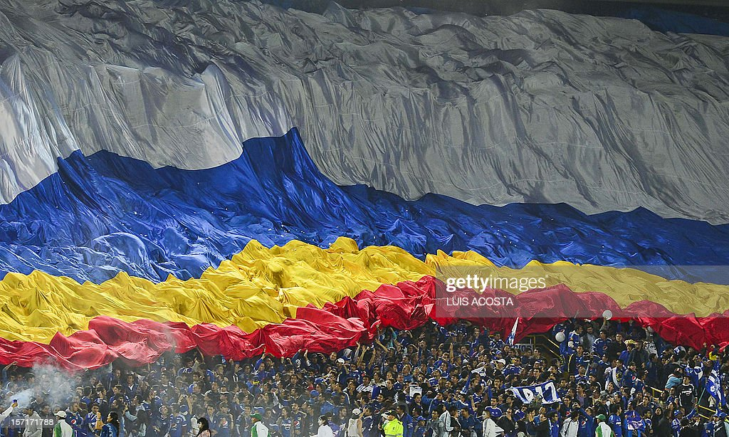 Fans of Colombian Millonarios unveil a giant flag before their 2012 Copa Sudamericana semifinal football match against Argentine Tigre at El Campin stadium in Bogota on November 29, 2012. AFP PHOTO / Luis Acosta