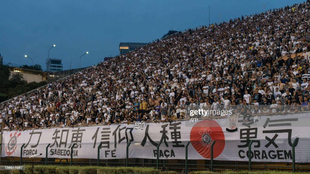 Fans of Corinthians display a banner which is associated with Japanese flag, beraing Chinese characters, Kanji, redaing force, wisdom, faith, race and bravery, during their their Brazilian championship football match against Santos at Pacaembu stadium in Sao Paulo, Brazil on Novemeber 24, 2012. Corinthians will play in FIFA Club World Cup in Japan from December 6. AFP PHOTO/Yasuyoshi CHIBA