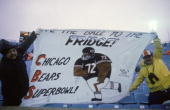 Fans of defensive lineman William Perry of the Chicago Bears display a banner which reads 'Give the Ball to the Fridge' during a game between the...