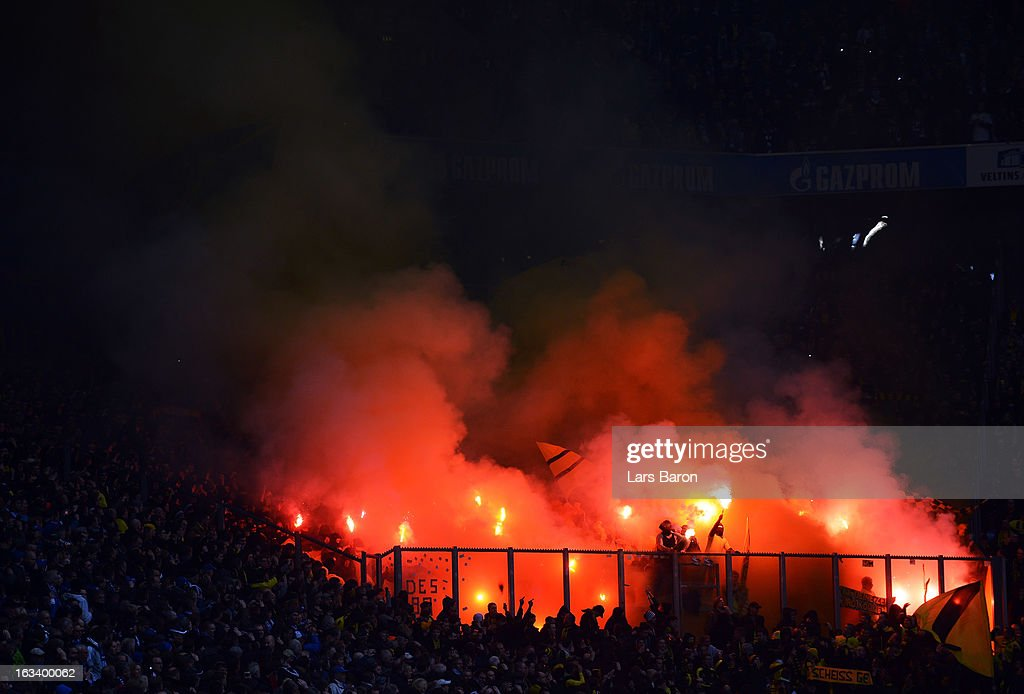 Fans of Dortmund blur flares during the Bundesliga match between FC Schalke 04 and Borussia Dortmund at Veltins-Arena on March 9, 2013 in Gelsenkirchen, Germany.