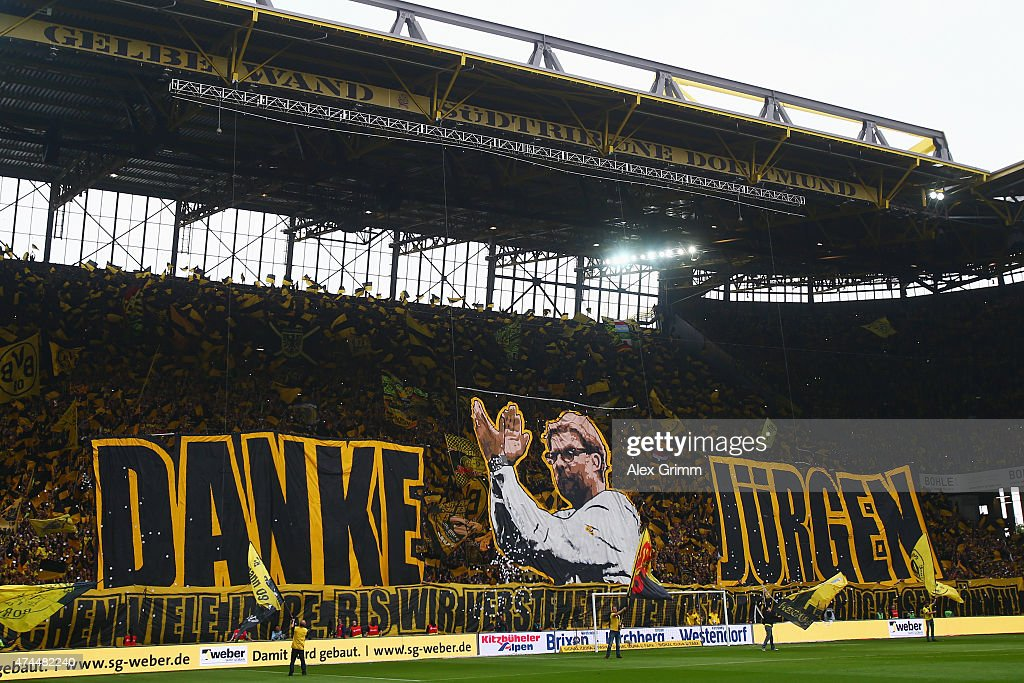 Fans of Dortmund hold up a banner for their team's head coach Juergen Klopp reading 'Thank you Juergen' prior to the Bundesliga match between...