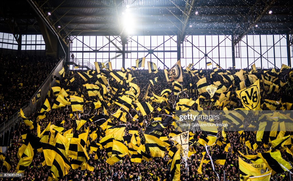 Fans of Dortmund wave their flags prior to the Bundesliga match between Borussia Dortmund and FC Schalke 04 at Signal Iduna Park on November 25, 2017 in Dortmund, Germany.