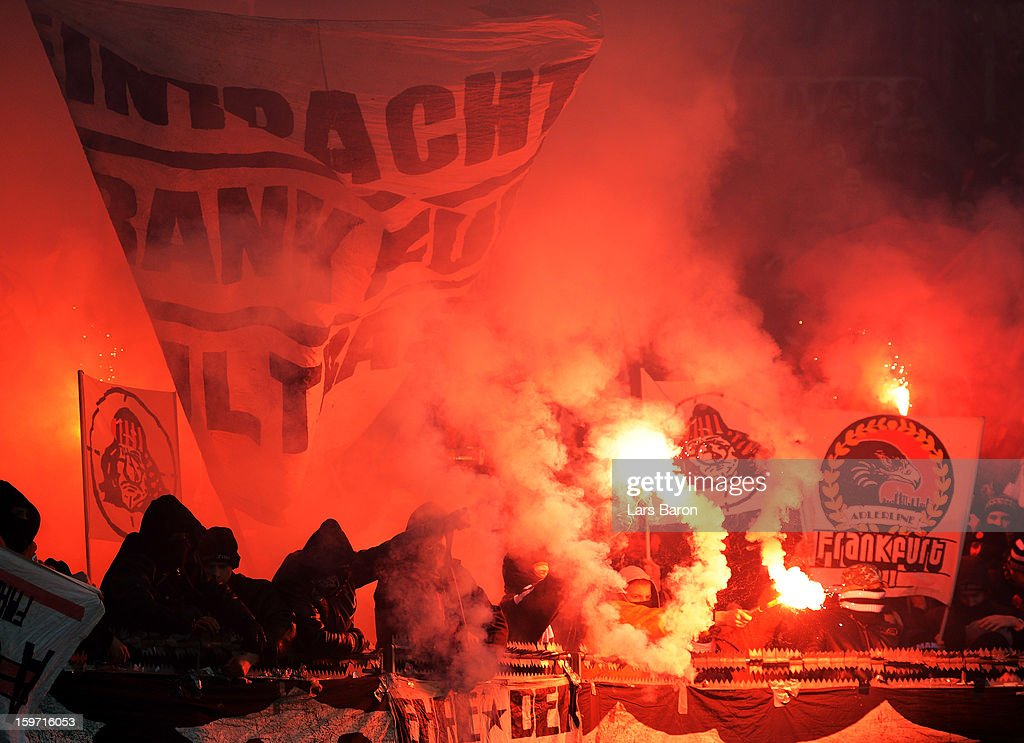 Fans of Frankfurt burn flares and throw firework during the Bundesliga match between Bayer 04 Leverkusen and Eintracht Frankfurt at BayArena on January 19, 2013 in Leverkusen, Germany.