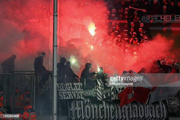 Fans of Gladbach throw smokebombs during the Bundesliga match between 1 FC Koeln and Borussia Moenchengladbach at RheinEnergieStadion on November 25...