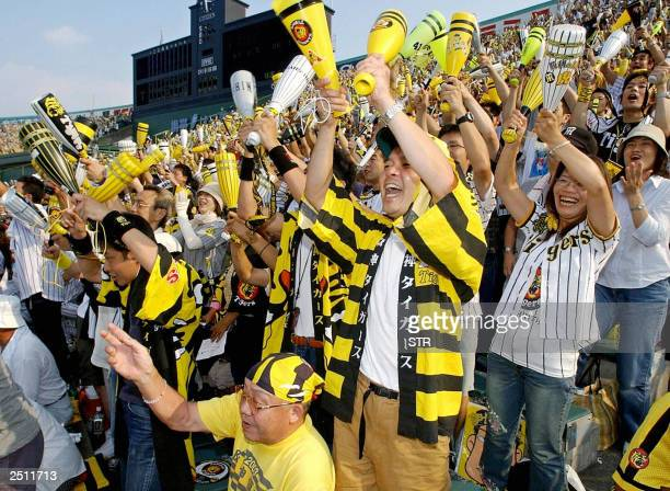 Fans of Hanshin Tigers celebrate as the team clinched their first league championship in 18 years at the Koshien stadium in Nishinomiya near Osaka...