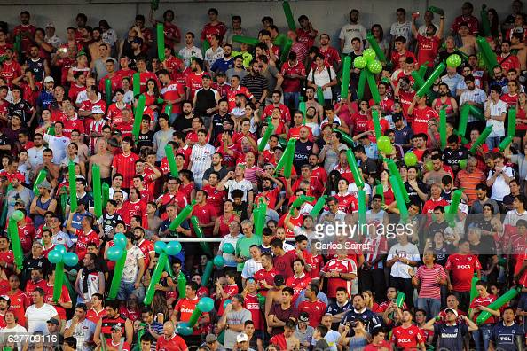 Fans of Independiente cheer for their team and display green ballons in memory of the victims of Chapecoense soccer team during a match between...