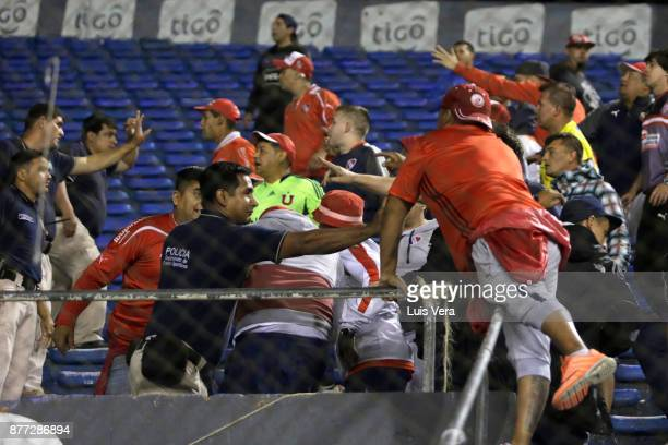 Fans of Independiente clash with the police during a first leg match between Libertad and Independiente as part of the semifinals of Copa CONMEBOL...