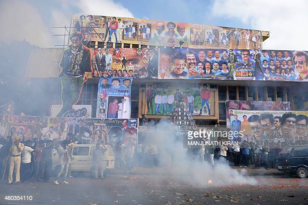 Fans of Indian film actor Rajinikant burst firecrackers during celebrations at a movie theatre in Bangalore on December 12 2014 on the occasion of...