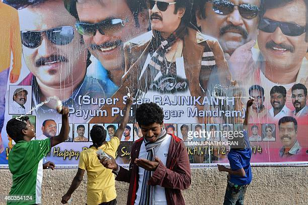 Fans of Indian film actor Rajinikant splash milk on his poster during celebrations at a movie theatre in Bangalore on December 12 2014 on the...