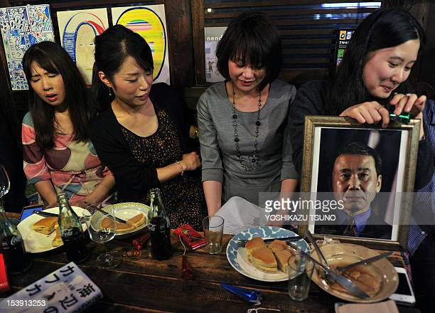 Fans of Japanese author Haruki Murakami react after learning that Murakami did not win the Nobel literature prize in a cafe in Tokyo on October 11...