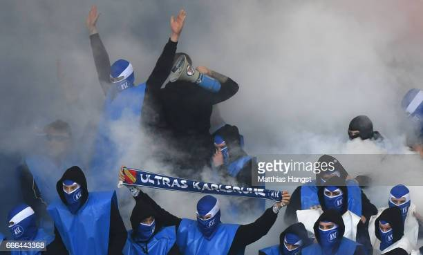 Fans of Karlsruhe burn flares prior to the Second Bundesliga match between VfB Stuttgart and Karlsruher SC at MercedesBenz Arena on April 9 2017 in...