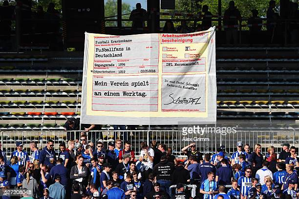 Fans of Karlsruhe hold up a fake sick certificate to protest against Bundesliga matches scheduled on Mondays prior to the Second Bundesliga match...