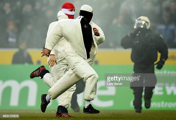 Fans of Koeln are running on the pitch after loosing the Bundesliga match between Borussia Moenchengladbach and 1 FC Koeln at Borussia Park Stadium...