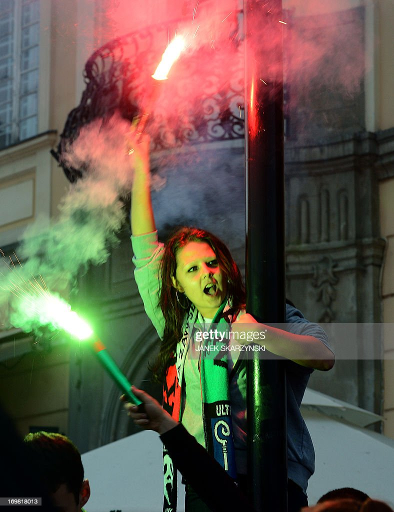 Fans of Legia Warszawa burn flares as they celebrate their club's victory and winning the champion of Poland title on June 2, 2013 in the old town in Warsaw.