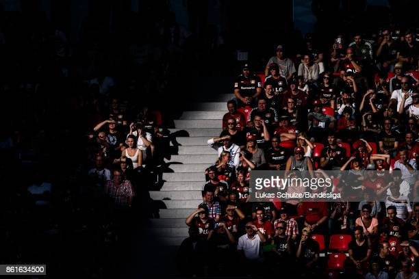 Fans of Leverkusen are lit by the sun during the Bundesliga match between Bayer 04 Leverkusen and VfL Wolfsburg at BayArena on October 15 2017 in...