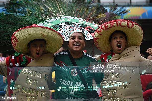 Fans of Mexico cheer before a Group A football match between Croatia and Mexico at the Pernambuco Arena in Recife during the 2014 FIFA World Cup on...