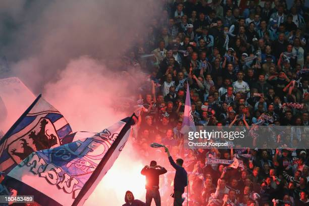 Fans of Muenchen throw smoke bombs during the Second Bundesliga match between VfR Aalen and 1860 Muenchen at ScholzArena on September 13 2013 in...