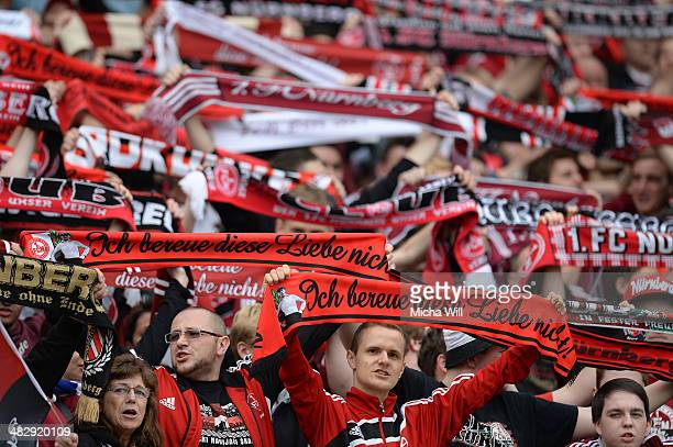 Fans of Nuernberg raise their scarves at the beginning of the Bundesliga match between 1 FC Nuernberg and Borussia Moenchengladbach at Grundig...