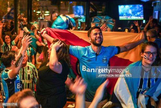 TOPSHOT Fans of of Brazil's Gremio watch their team during the 2017 Copa Libertadores final match against Argentina's Lanus at a bar in Porto Alegre...