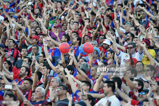 Fans of Paraguay's Cerro Porteno cheer for their team during the Paraguayan Clausura tournament final football match against Guarani on December 2 at...