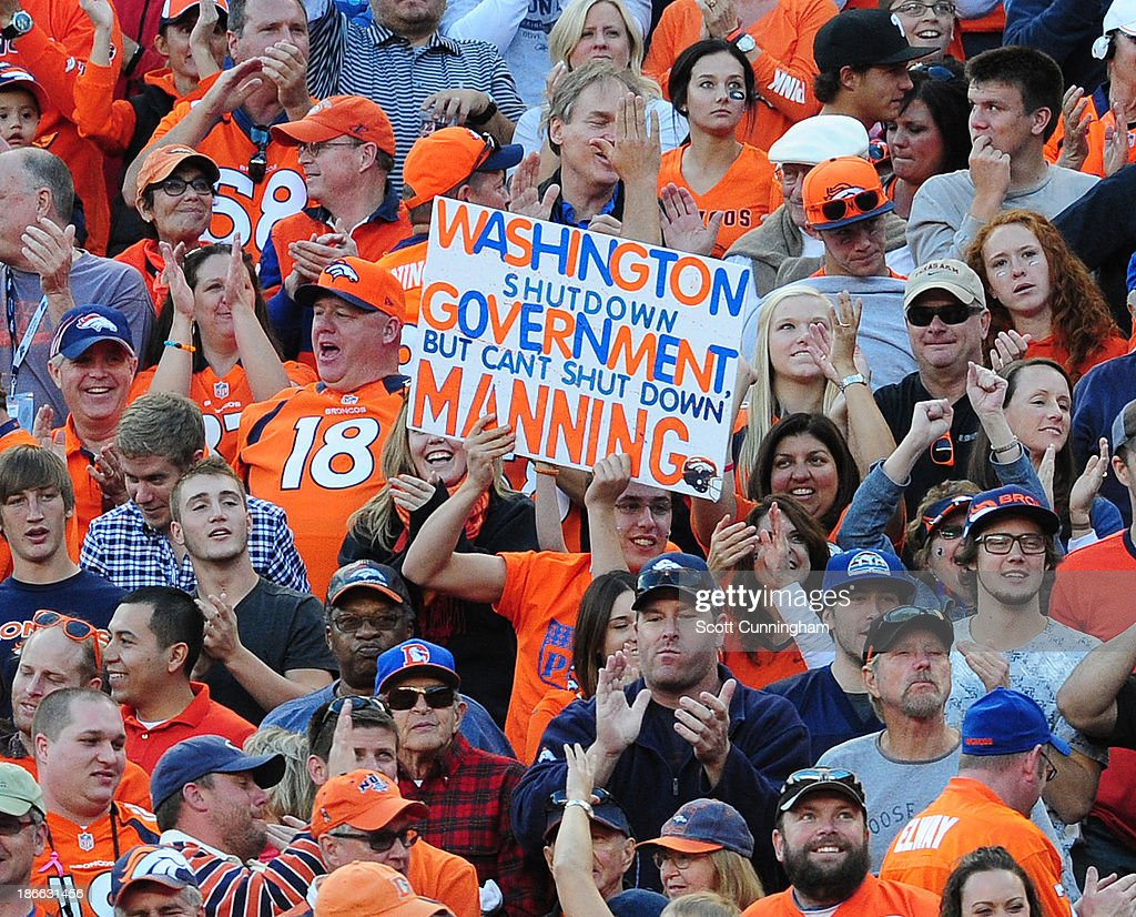 Fans of Peyton Manning #18 of the Denver Broncos celebrate after a score against the Washington Redskins at Sports Authority Field on October 27, 2013 in Denver, Colorado.