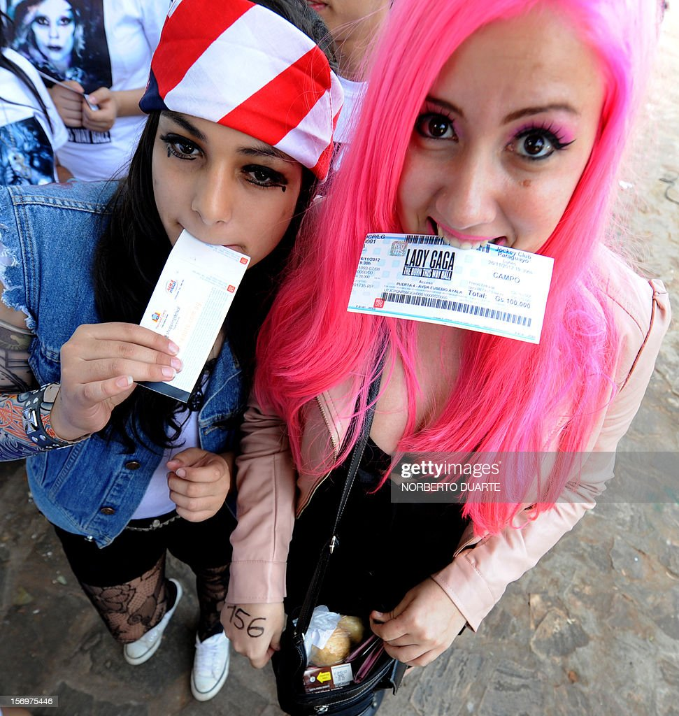 Fans of pop diva Lady Gaga, currently on tour in South America, show their tickets as they queue waiting to get inside the venue for the show the singer will offer in the Paraguayan capital, Asuncion, on November 26, 2012. AFP PHOTO/NORBERTO DUARTE