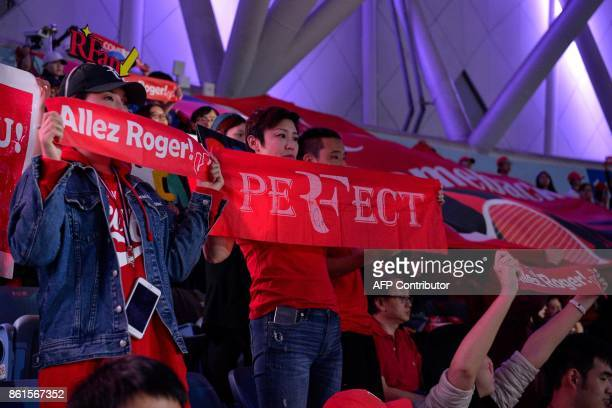 Fans of Roger Federer of Switzerland hold banners and posters during his men's singles final match against Rael Nadal of Spain at the Shanghai...
