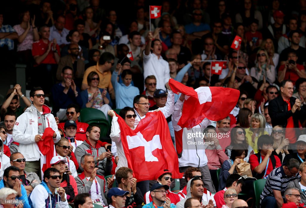 Fans of Roger Federer of Switzerland hold up the Swiss Flag as Federer takes on Juan Martin Del Potro of Argentina in the Semifinal of Men's Singles Tennis on Day 7 of the London 2012 Olympic Games at Wimbledon on August 3, 2012 in London, England.