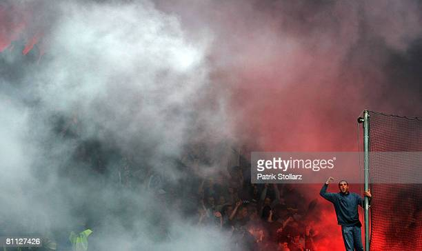 A fans of Rostock cheers in the fog of a granate fired up from Rostock fans prior the Bundesliga match between VfL Bochum and FC Hansa Rostock at the...