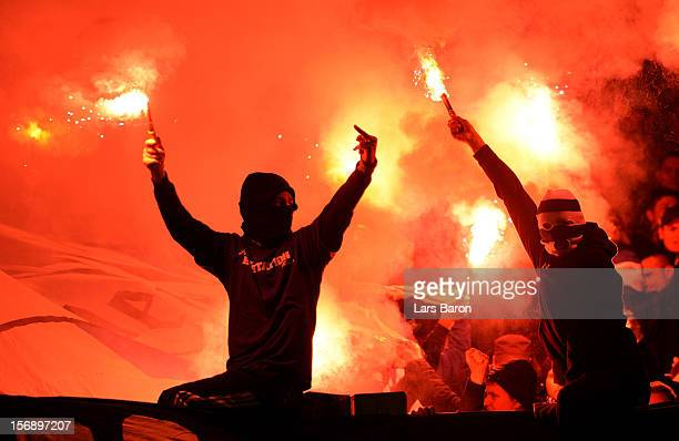 Fans of Schalke burn flares during the Bundesliga match between FC Schalke 04 and Eintracht Frankfurt at VeltinsArena on November 24 2012 in...