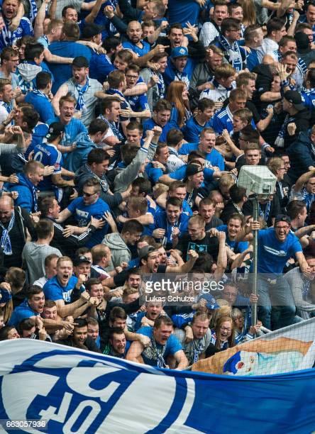 Fans of Schalke celebrate their teams first goal during the Bundesliga match between FC Schalke 04 and Borussia Dortmund at VeltinsArena on April 1...