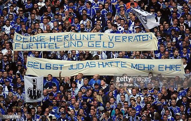 Fans of Schalke hold a banner against former goalkeeper Manuel Neuer during the Bundesliga match between FC Schalke 04 and FC Bayern Muenchen at...