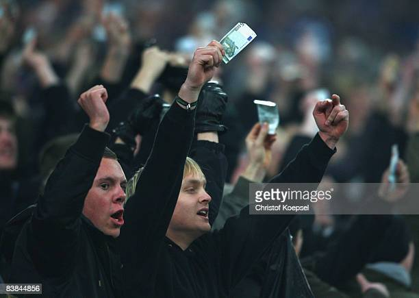 Fans of Schalke vent their displeasure waving bank notes after the second goal of Manchester City during the UEFA Cup Group A match between FC...