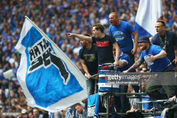 Fans of Schalke yell at the players of Borussia Dortmund during the Bundesliga match between FC Schalke 04 and Borussia Dortmund at VeltinsArena on...
